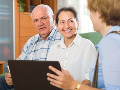Older man and woman sitting together smiling at another woman who is showing them something on a laptop