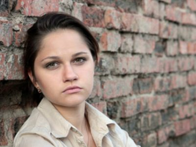 Young Woman leaning against an old brick wall, looking at the camera