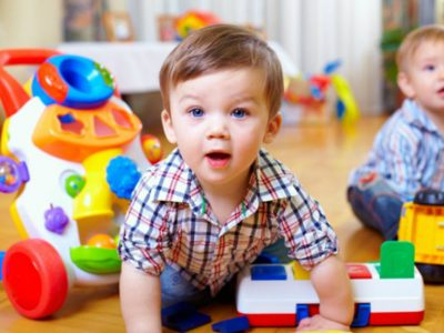 two toddlers playing with plastic toys, one toddler in focus at the front with blue eyes.
