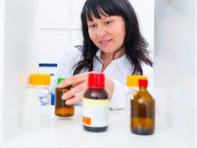 Woman in white shirt with bottles of prescription drugs