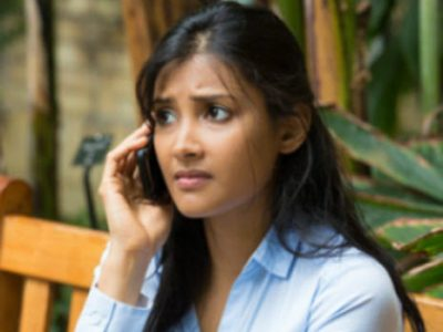worried looking asian woman on the phone wearing a light blue blouse