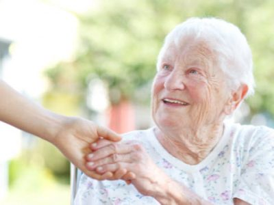 Elderly lady in flowery top holds the hand of a younger person in a garden