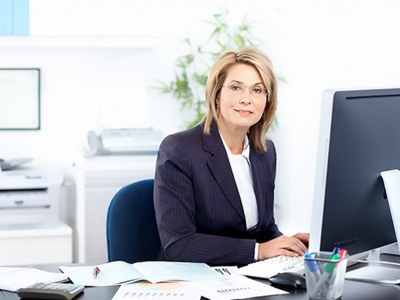 Blonde woman in business attire sits at an office desk covered in paperwork, working on her computer