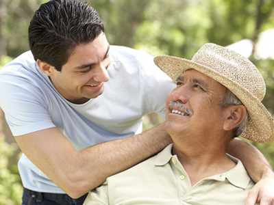 Young man with white shirt gazes adoringly at older gentleman wearing a straw hat, in a summer garden