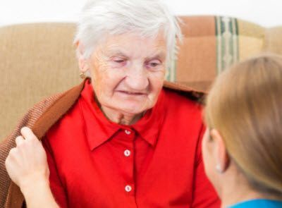 Elderly female in a red shirt talks to a young nurse who is helping to keep her warm