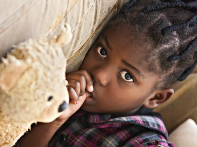 Sad, young black girl sucking thumb while lying on a sofa with a teddy bear lying next to her