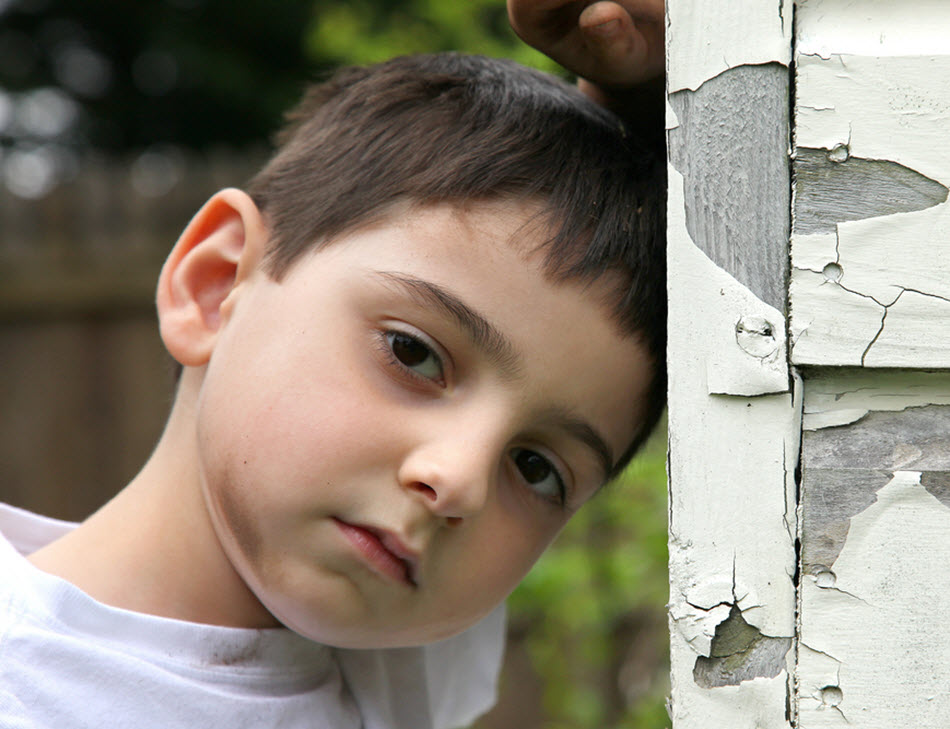 Sad young child with dirty face leaning against old shed with white peeling paint