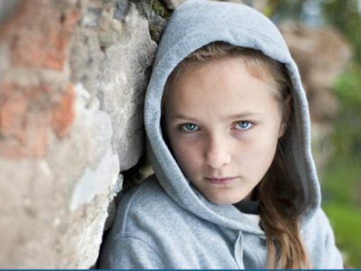 A young girl wearing a light grey hoody, with the hood up, leaning against an old stone wall