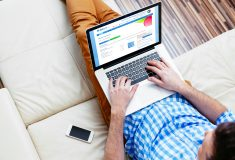 Man sitting on a sofa with a laptop, using Me Learning's Blue LMS