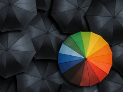 mulitple black umbrella's with one multi coloured umbrella