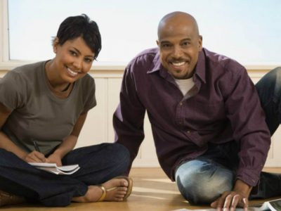Black couple sat on the floor, woman in writing in a note pad, both are looking at the camera smiling