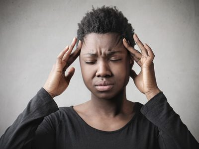 Black woman with a headache holding her temples