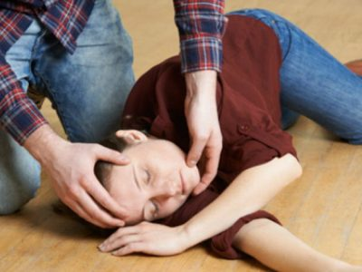 Unconscious woman on the floor in teh recovery position, man opening her airways