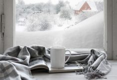 cup of tea/coffee on a book, with a scarf, in front of a window with a snowy scene in the background