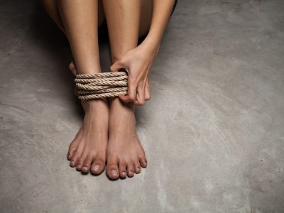 female legs bound with natural rope as girl sits on concrete floor