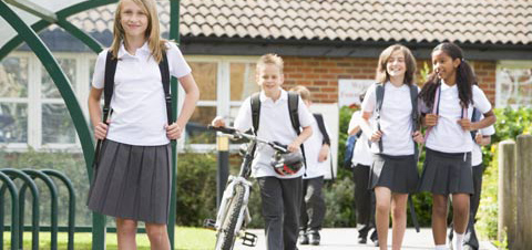 happy schoolchildren (one pushing a bicycle) in uniform walk out of school