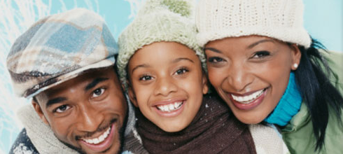 black family in winter clothing and wool hats look happily at the camera