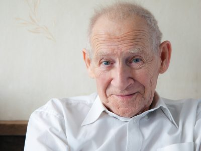 An elderly man in a white shirt smiles and looks into the camera