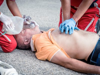 A man in an orange shirt receives CPR first aid from two paramedics