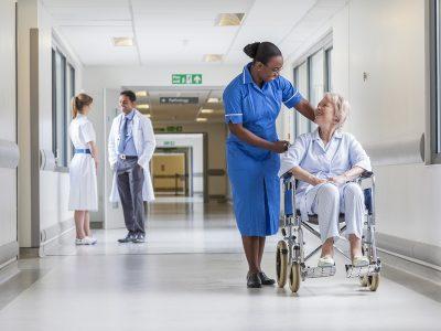 A nurse pushes a female patient down a corridor in a wheelchair