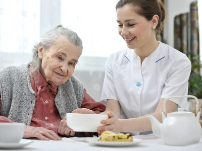 Young female nurse places breakfast down in front of an elderly resident