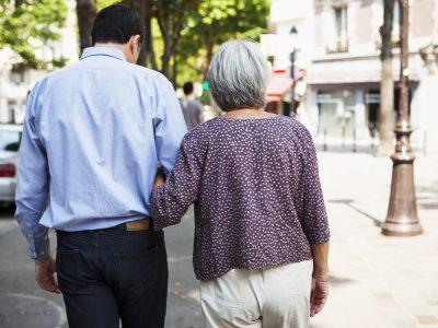 A gentleman helps an elderly woman walk through a town centre
