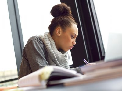 A woman studying in a library, writing on a notepad