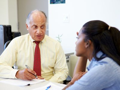 An elderly gentleman speaking to a young woman and assessing her performance in an appraisal