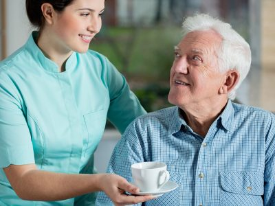 A nurse hands a happy elderly man a cup of tea