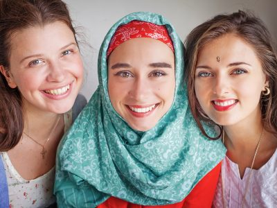 Three happy girls wearing garments from different cultures