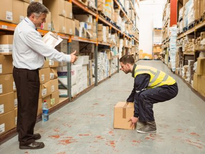 A worker demonstrates the correct way of manual handling, as a supervisor smiles and gives him a thumbs up