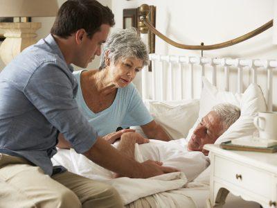 A gentleman lies in bed, suffering from illness, as worried relatives comfort him