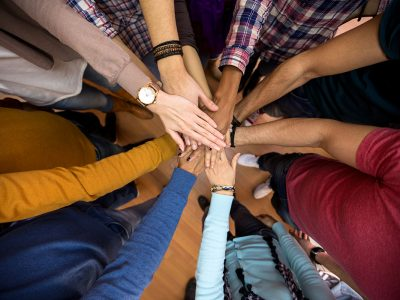 A diverse group of individuals with their hands held together in the centre of a circle