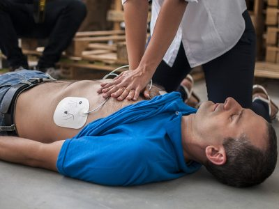 Man in blue shirts receives CPR first aid from a member of staff