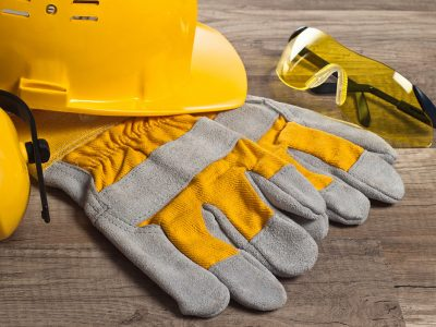 PPE, yellow gloves, hard hat, glasses and ear protectors on wood