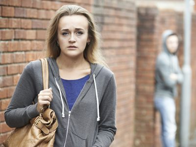teenage girl with brown leather handbag looking worried, with blurred out person in the background
