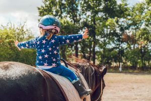 child on a horse wearing a helmet and boots what Horse Riding gear do newbies need