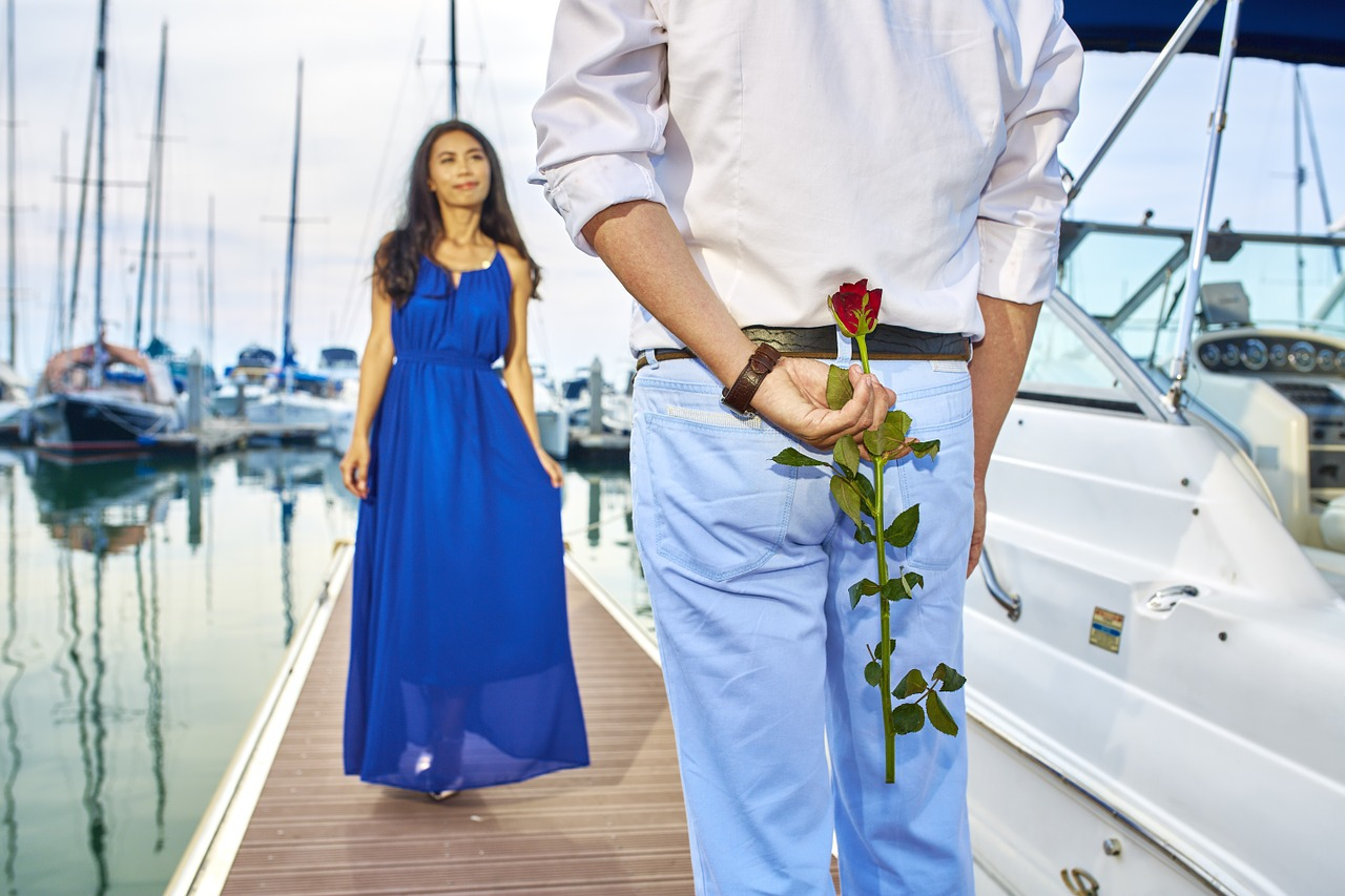 Man holding rose behind his back - Planning a Couples Retreat