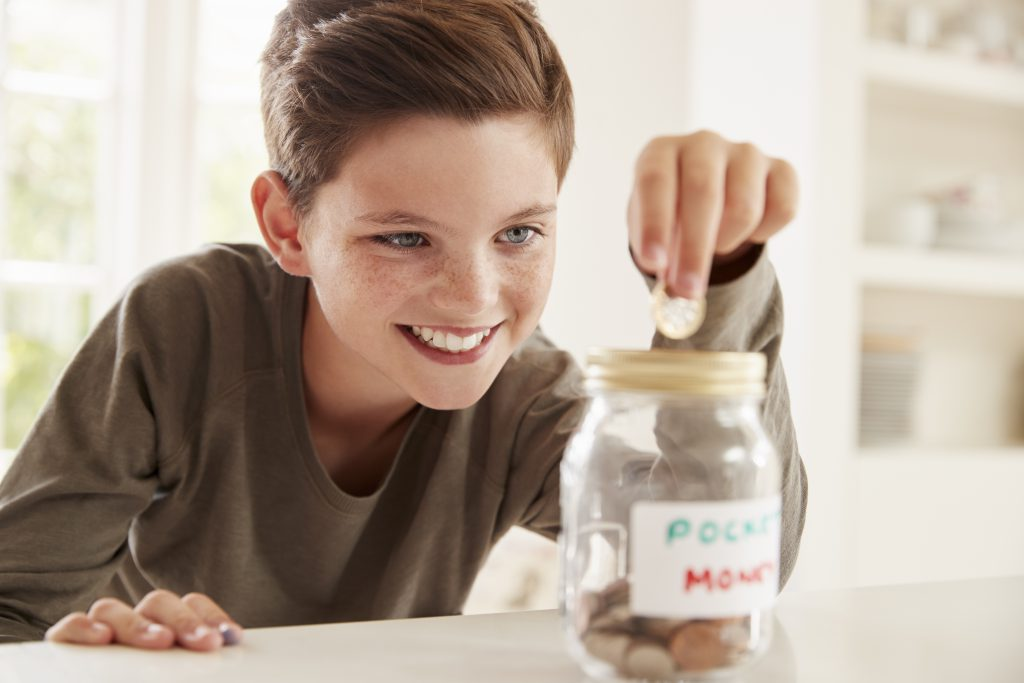 Providing Financial Security For Our Children - boy putting money in jar