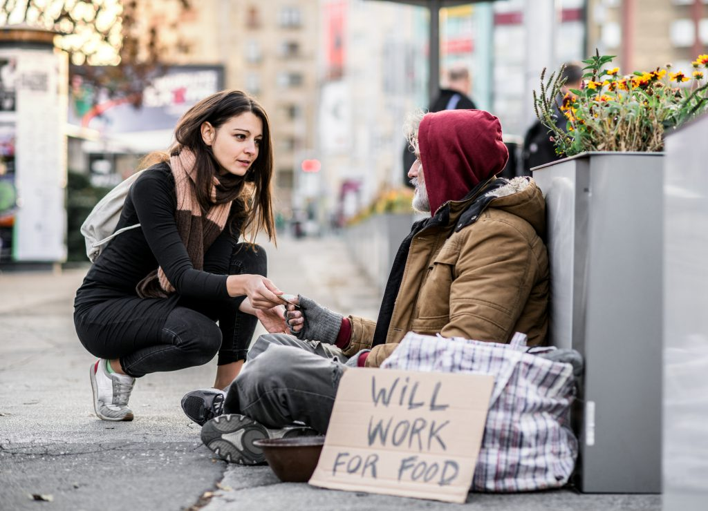 teach kids the value of money - girl giving homeless man some money