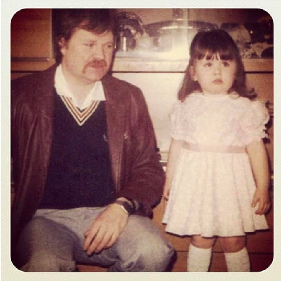 A photo of My Dad with his Auburn hair and moustache, and me in a pink frilly dress in 1986.