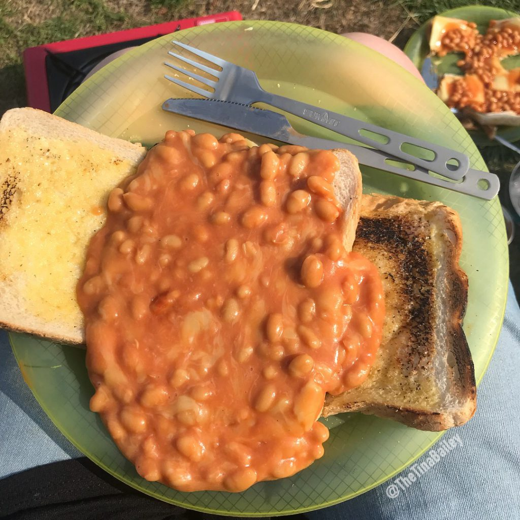 green plastic plate with beans on toast on it - camping food
