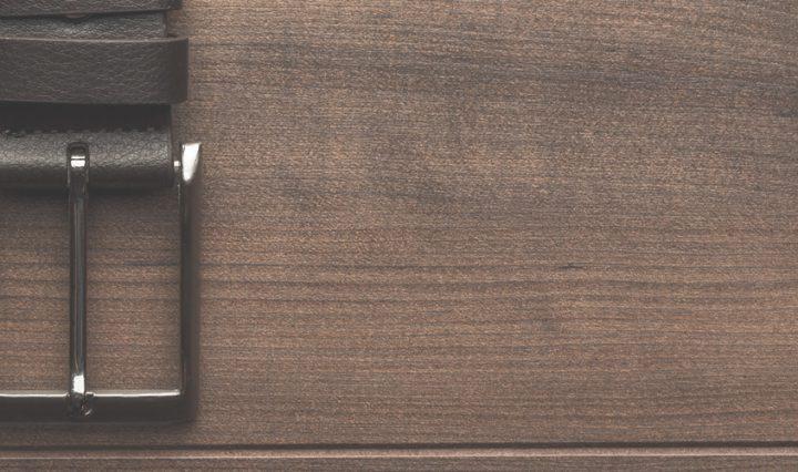 mens belt buckle on brown wood background