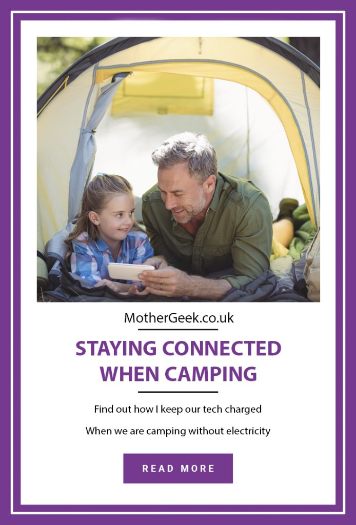 Dad and daughter using phone in tent - staying connected when camping