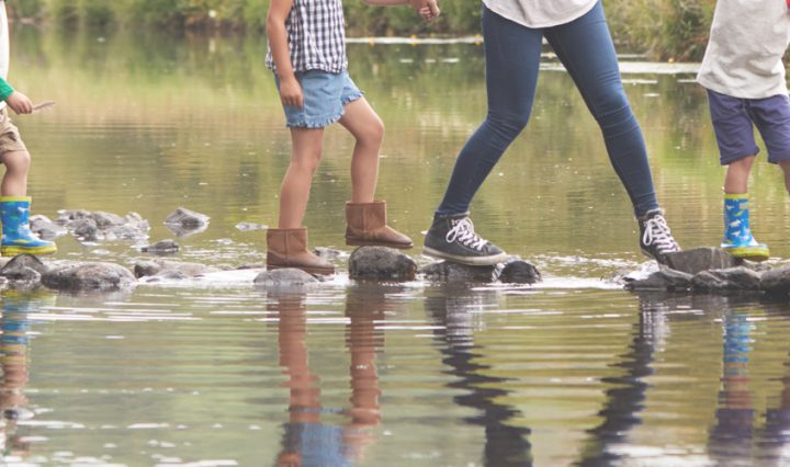 free UK family days out - family crossing stepping stones across river