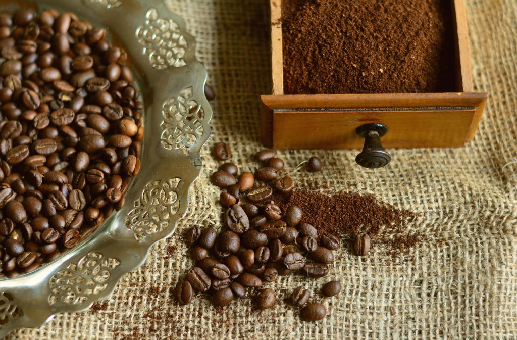 coffee beans in a dish, ground coffee in a drawer and some on the table