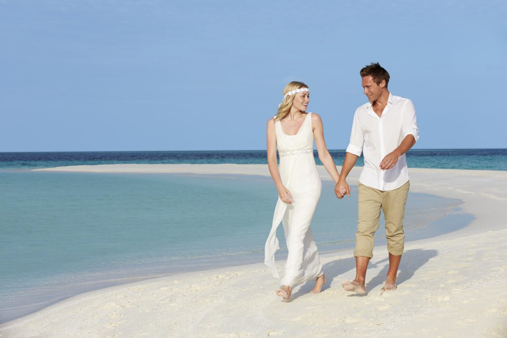 bride and groom, barefoot on the beach. tips for choosing your wedding shoes