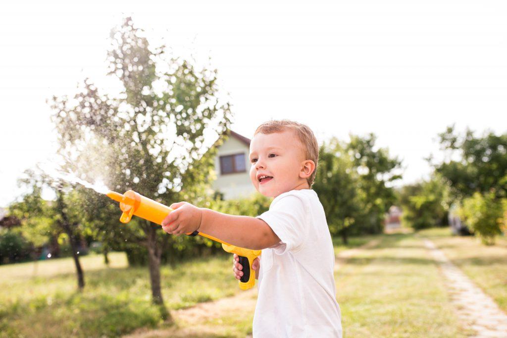young boy firing water gun - ,toys that get kids outdoors