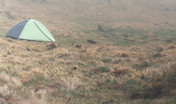 tent on a hill on a misty morning - tips for camping in the rain