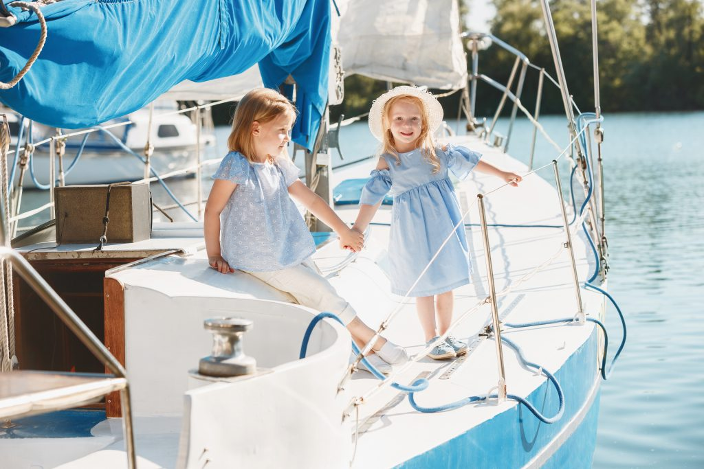 Boating Holidays with Children - two young girls sat on a yacht